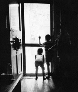 Black and white photo of children looking out an open door