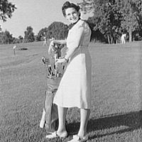 Woman with clubs on golf course